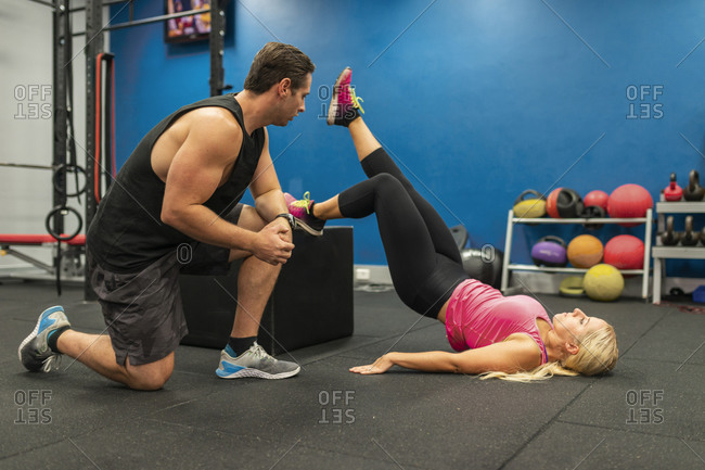 Trainer helping a woman workout in a gym