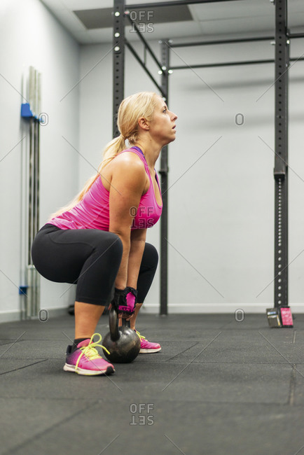 Woman lifting a kettlebell in a gym