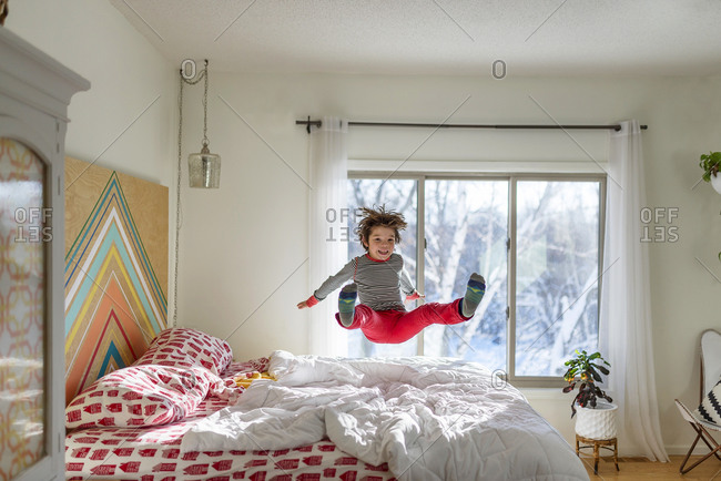 Little boy in red pants jumping on a bed