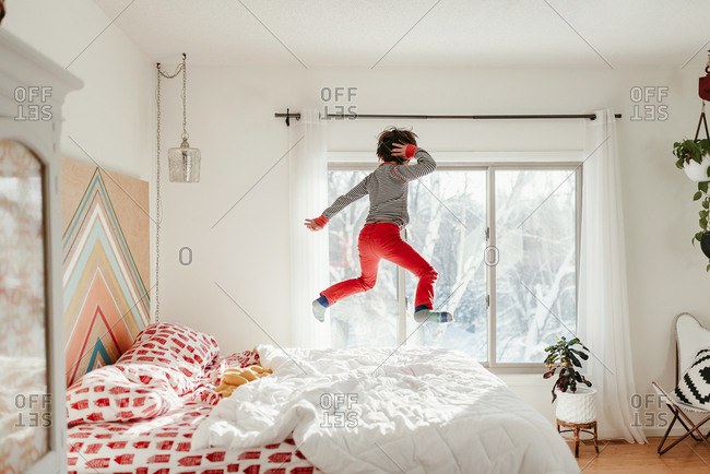 Young boy in red pants posing while jumping on a bed