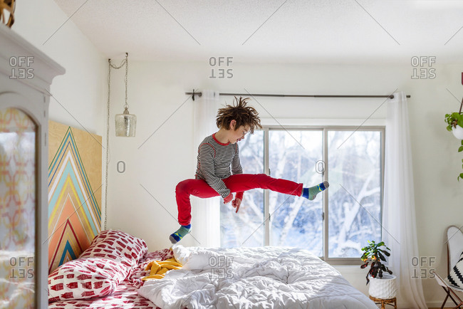 Young boy in red pants jumping on a bed pretending to be a rock star