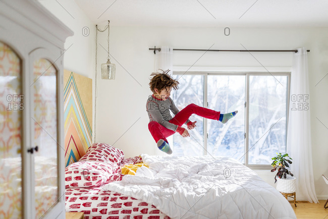 Young boy in red pants jumping on a bed pretending to be a play guitar