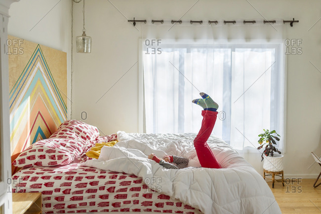 Young boy in red pants flopping on a bed