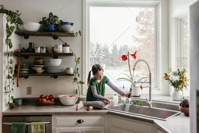 Young girl sitting beside the sink in the kitchen
