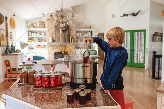 A young boy canning some jam