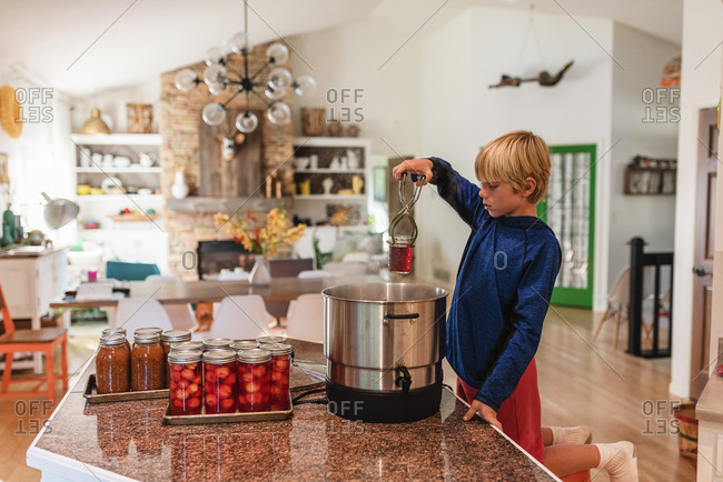 A young boy canning homemade jam