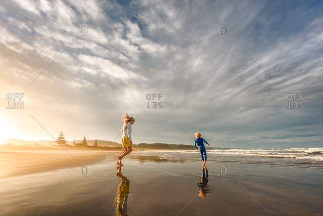 Brother and sister playing in the tide on a beach in New Zealand