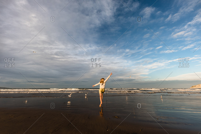 Girl chasing birds on a beach in New Zealand