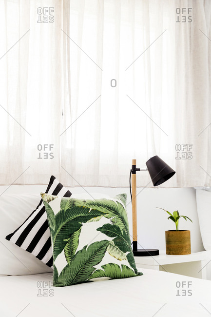 Pillows on a wooden bench beside plant and lamp