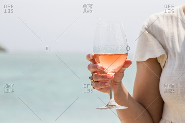 Woman having a glass of wine at an oceanside resort