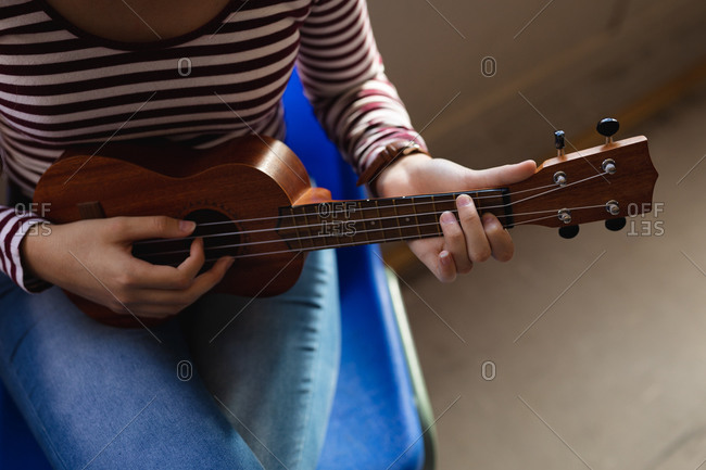 High angle mid section of a Caucasian musician teenage girl wearing a striped sweater sitting and playing a ukulele alone