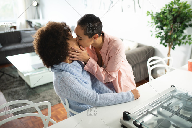 Front view of mixed race female couple relaxing at home, embracing and kissing passionately in their kitchen sitting at the kitchen island