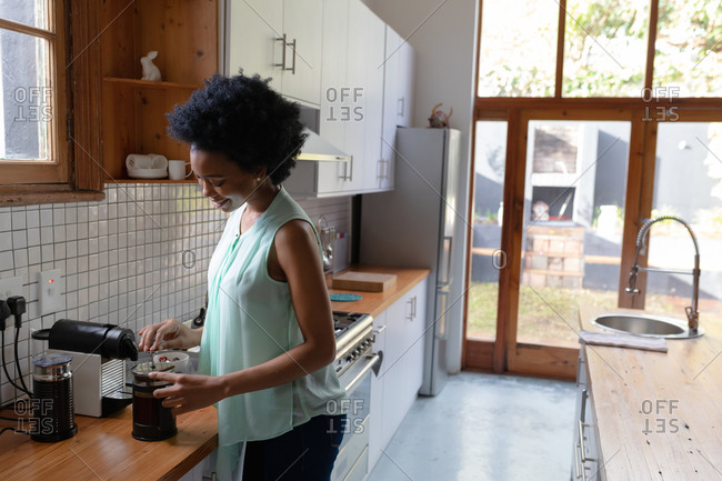 Side view of an attractive African American woman at home, standing in the kitchen preparing coffee in a cafetiere. She is smiling and enjoying her weekend.