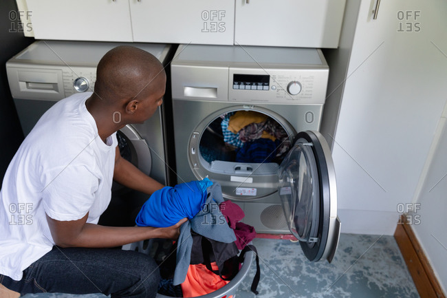 High angle view of an African American man at home, kneeling down and putting laundry in a washing machine from a laundry basket.