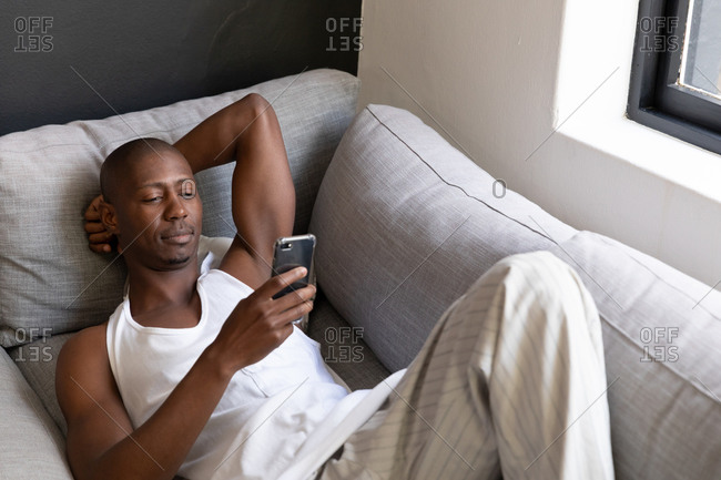 Front view of an African American man wearing a white vest reclining on a couch using a smartphone in the living room