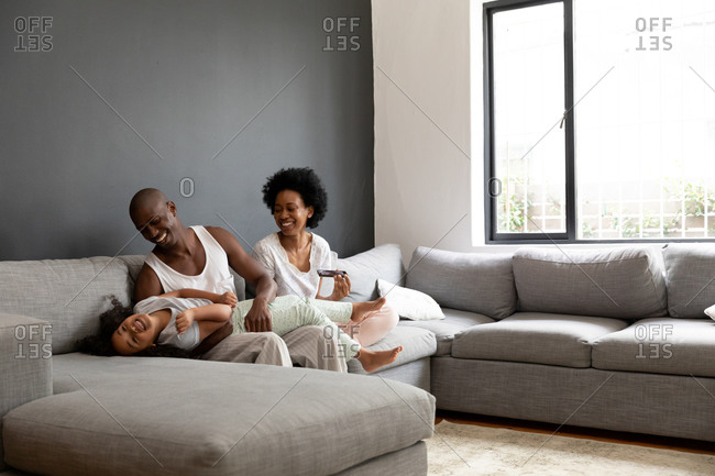 Front view of an African American couple and their young daughter relaxing in the living room together in the morning, the couple sitting on the sofa with the daughter lying across the lap of her father laughing