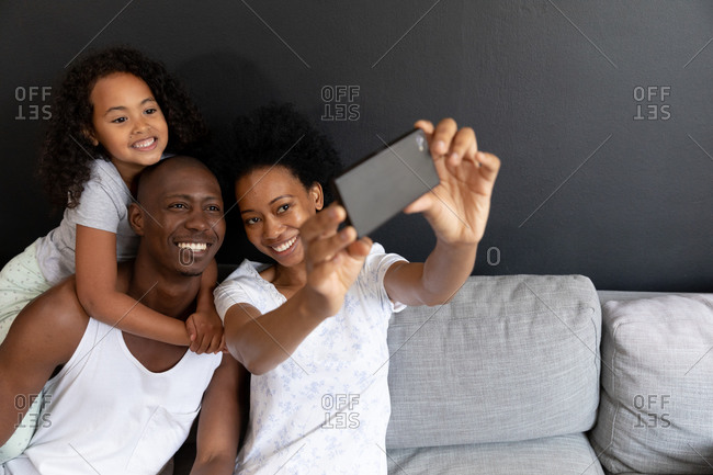 Front view of an African American couple and their young daughter relaxing in the living room together in the morning, the couple sitting on the sofa with the daughter standing behind her father with her hands arms around his neck, her mother using a smartphone and taking a selfie of them smiling together