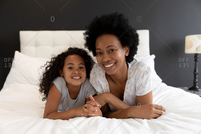 Portrait of an African American woman and her young daughter relaxing in the bedroom together, lying side by side on the bed and smiling to camera