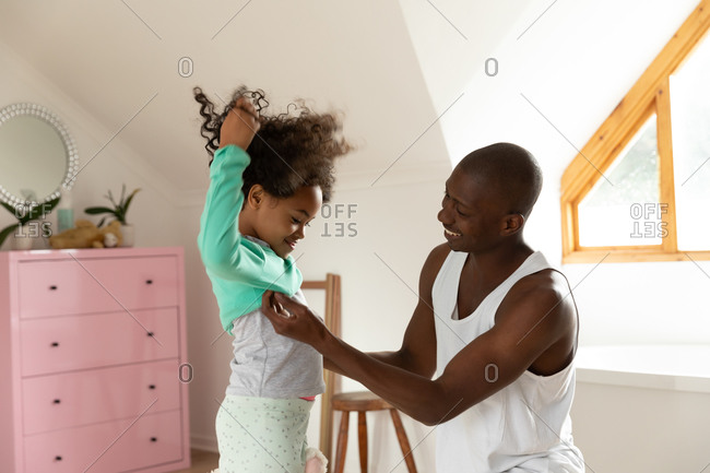 Side view of an African American man in the bedroom with his young daughter, helping her to get dressed. They are smiling.