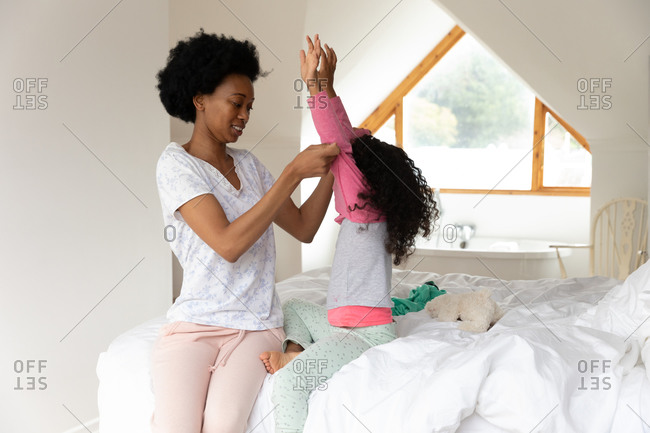 Side view of an African American woman in the bedroom with her young daughter, helping her to get dressed while sitting on the bed
