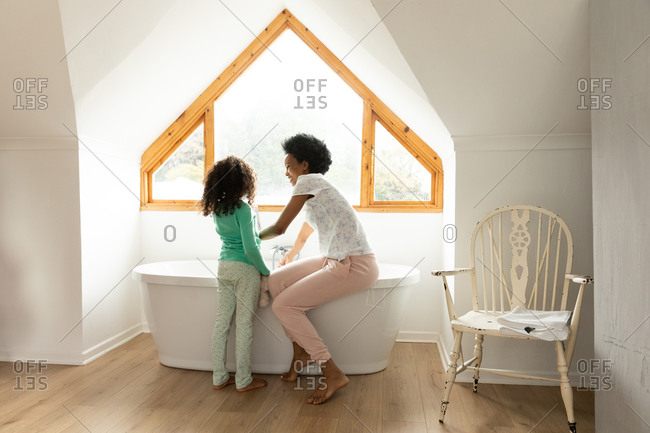 Side view of an African American woman and her young daughter in the bathroom, the mother sitting on the edge of the bathtub and running a bath, the daughter standing beside her