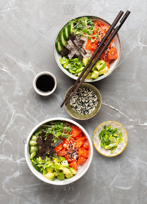 Two Poke bowls with salmon, avocado, spring onion and fresh cucumber