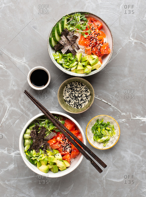 Two Poke bowls with salmon, avocado, seaweed and fresh cucumber