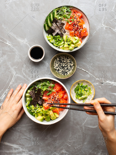 Woman eating Poke bowl. Female hands holding chopsticks eating Poke bowl with salmon and avocado