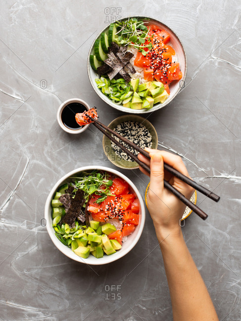 Woman eating Poke bowl. Female hand holding chopsticks deeping salmon in soy sauce