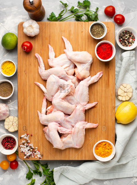 Ingredients for preparing spicy chicken wings. Raw chicken wings on wooden cutting board