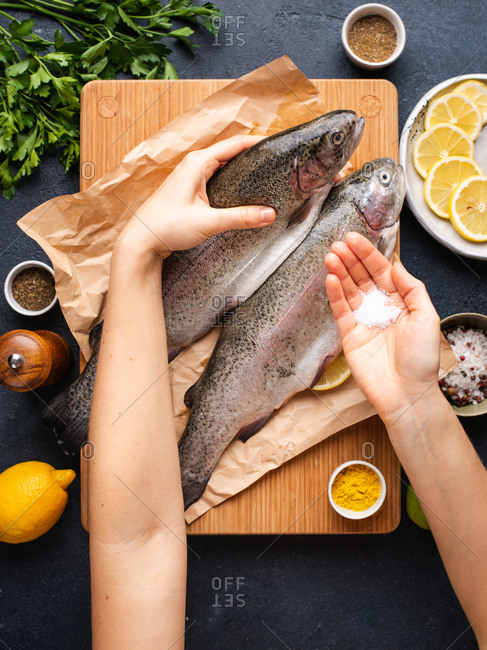 Woman preparing trout. Female hands holding raw fish and pinch of salt for salting