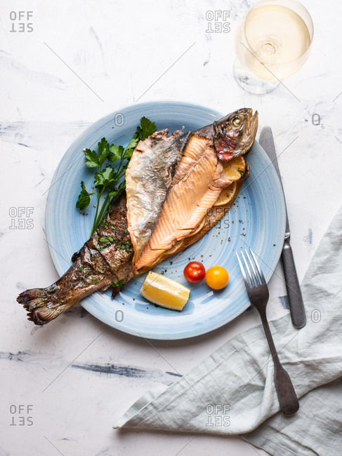 Cooked trout served on blue ceramic plate with tomatoes and parsley and glass of white wine