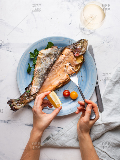 Cooked trout served on blue ceramic plate with glass of white wine. Female hands holding fork and lemon