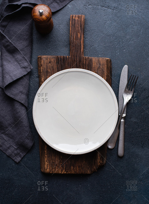 Overhead view of empty ceramic plate with fork and knife