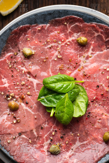 Close-up image of Beef Carpaccio served with capers and spinach leaves