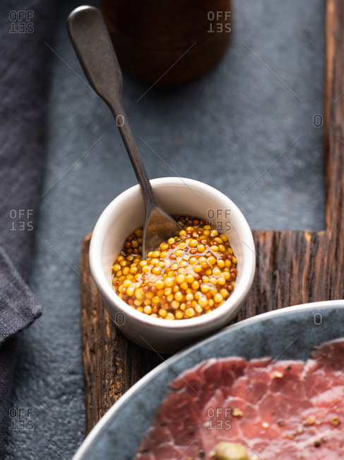 Close-up of mustard sauce in ceramic bowl served for Beef Carpaccio