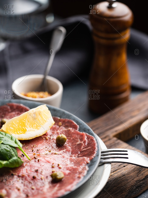 Close-up image of Beef Carpaccio served on the plate with capers, lemon and spinach leaves