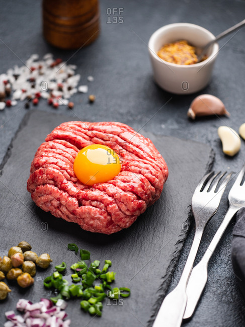 Beef tartare steak served with ingredients on slate