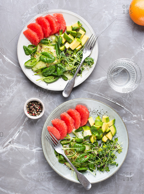 Overhead view of salad with grapefruit, avocado, cucumber, spinach, meant leaves and micro greens