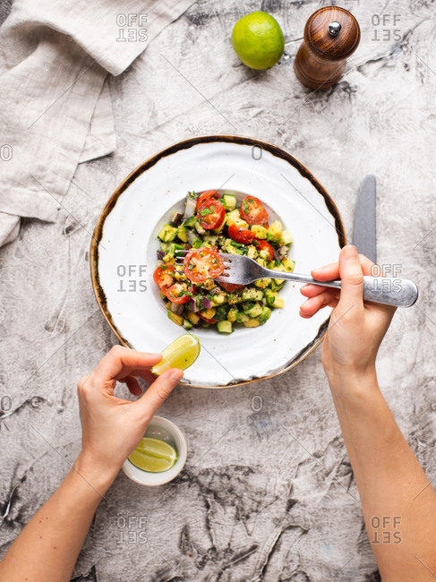 Woman eating avocado salad with cherry tomatoes. Hand holding fork above plate with salad