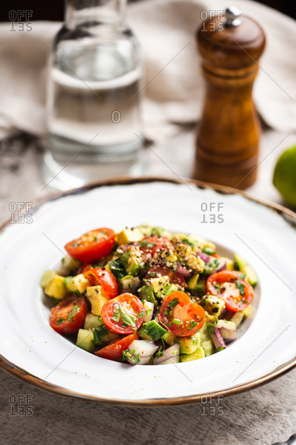 Plate with avocado salad with cherry tomatoes, red onion and fresh cucumber