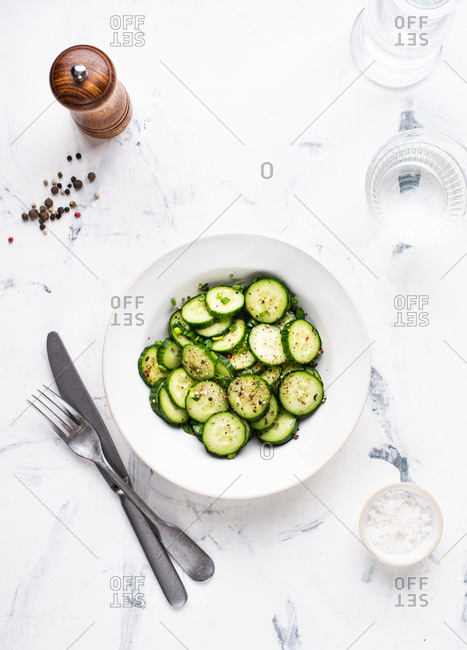 Overhead view of cucumber salad with spring onion served in white ceramic bowl