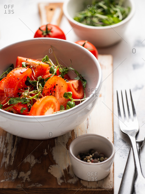 Tomato salad with ground pepper, olive oil and microgreens served in ceramic bowl