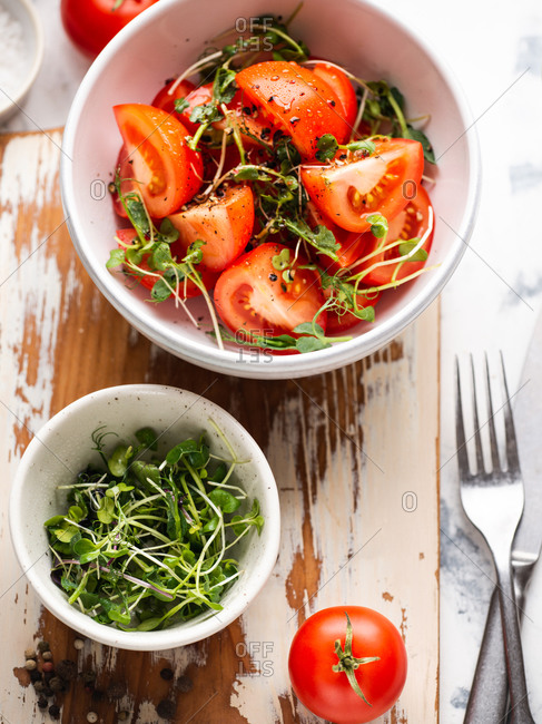 Tomato salad with ground pepper, olive oil and microgreens