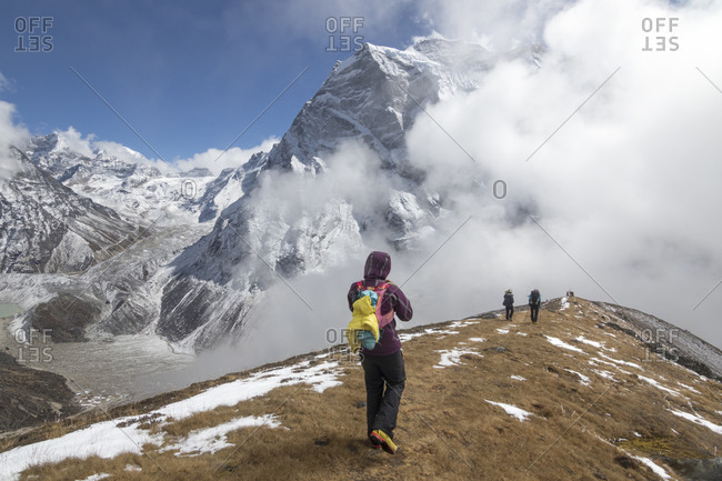 A woman descends a gentle ridge into the fog, Himalayan peaks in back