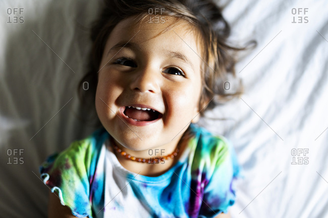 Little girl with colorful top lying in bed