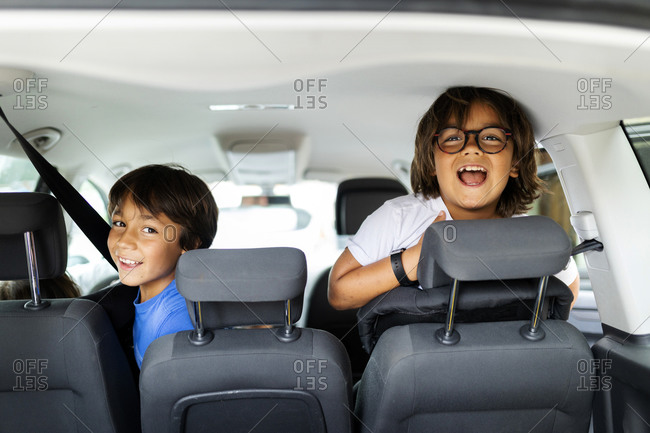 Little boys riding in back seat of car