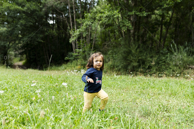 Carefree little girl running on meadow