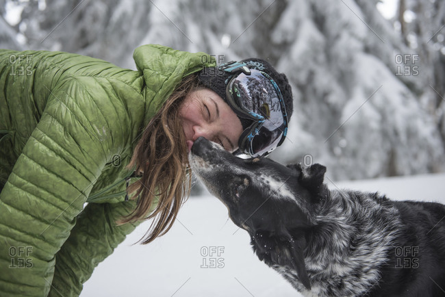 A dog licks its owner while outside skiing in the backcountry.