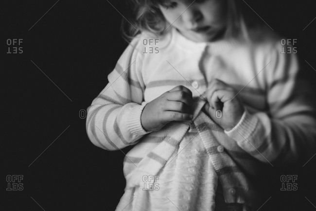 Toddler learning to button sweater